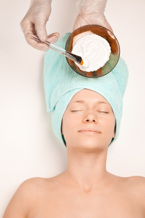 Young woman at spa procedures applying mask photo