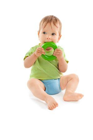 Adorable bebé muerde un juguete y se sienta en el suelo aislado en blanco