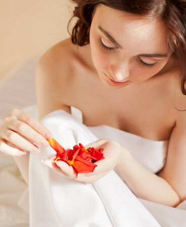 Beautiful sexy woman holding a rose petals in bed (focus on hands) photo
