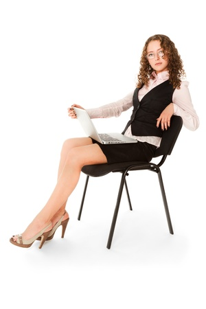 Young attractive woman with laptop sitting on the chair photo