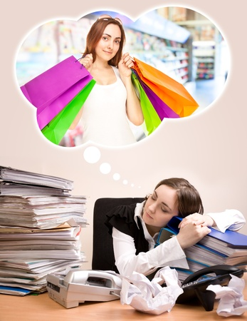 Young secretary with a lot of folders sleeping and dreaming of shopping photo