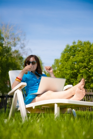 Beautiful woman lying in sun lounger and drinking photo