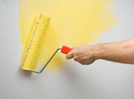 wall painting: Picture of a hand painting the wall with roller Stock Photo