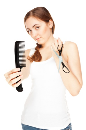Hairdresser holding a  scissors and comb isolated on white (focus on comb) photo