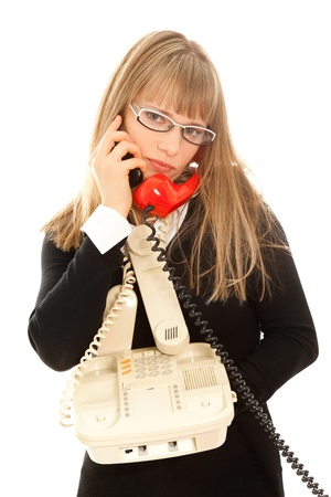 Displeasured businesswoman with telephones photo