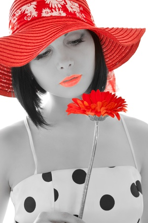 Woman looking on the red gerbera isolated on white photo