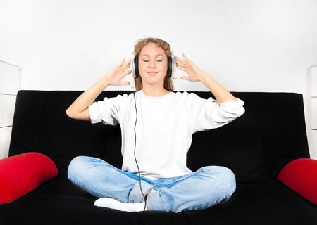 Beautiful woman in boyfriends jeans sitting on couch with headphones on her head photo