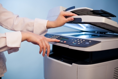 Womans hand with working copier photo