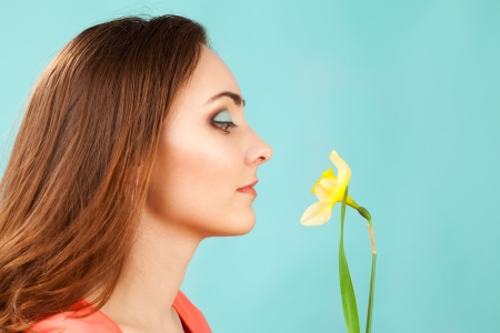 jonquil: Beautiful woman with makeup smelling narcissus on blue background Stock Photo