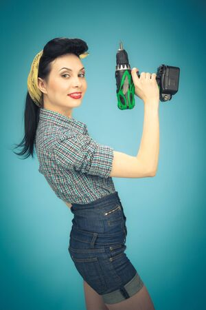 Picture of beautiful pin up woman with electric screwdriver photo