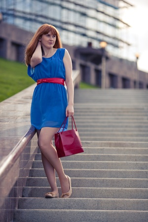 Beautiful woman with red shopping bag standing on the stairs Stock Photo - 20571742