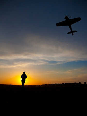 radio activity: Man silhouette with rc plane (focus on RC model)