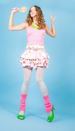 Pin-up woman with colorful lollipop smiling and dancing photo