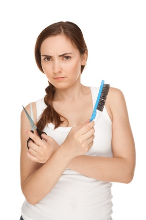 Anger woman with comb and sissors smiling isolated on white (focus on woman) photo