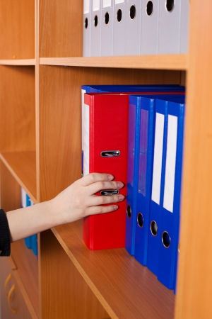 Womans hand taking a red folder from shelf photo