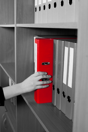 Woman's hand taking a red folder from shelf Stock Photo - 21447888