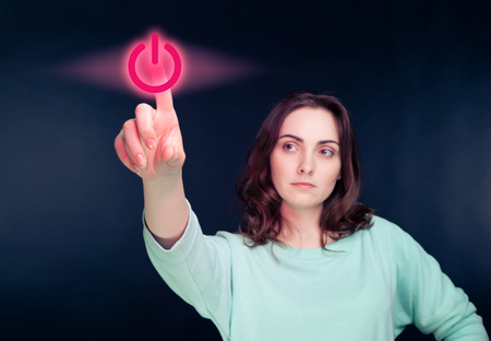 virtual reality simulator: Woman pointing her finger to virtual power button Stock Photo