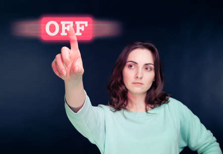 Woman pointing her finger to virtual off button Stock Photo - 22794933