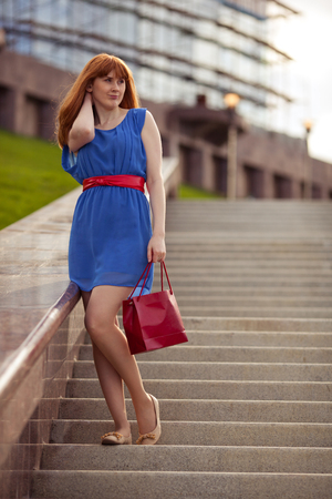 ginger haired: Beautiful woman with red shopping bag standing on the stairs Stock Photo