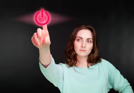 virtual reality simulator: Woman pointing her finger to virtual power button  focus on button  Stock Photo