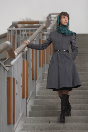 Beautiful stylish woman  in grey coat standing on stairs outdoors photo