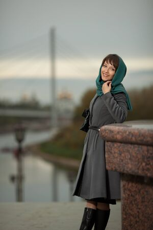 Beautiful stylish woman  in grey coat smiling outdoors photo