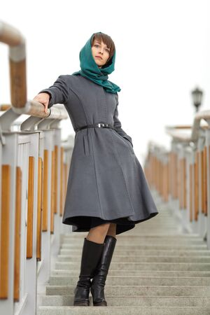 Beautiful stylish young woman  in grey coat standing on stairs photo