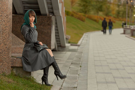 Beautiful stylish woman  in grey coat sitting and thinking outdoors photo