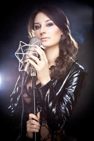 Picture of beautiful singer with studio microphone photo