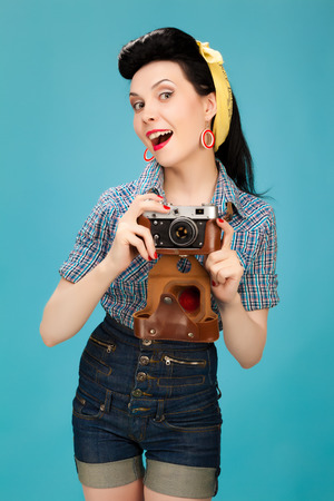 Retro pin-up woman with film camera on blue background photo