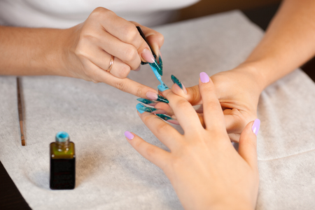 Beautician doing manicure with nail varnish photo