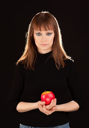 Beautiful woman with red apple on black background photo