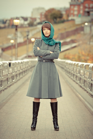 Beautiful stylish woman in grey coat looking straight photo