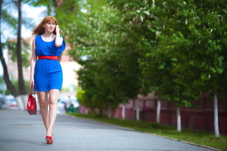 Beautiful ginger-haired woman in blue dress outdoors photo