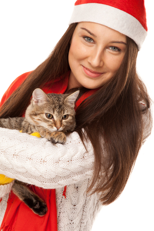 Beautiful young woman in santas hat with thoughtful kitten on her hands photo