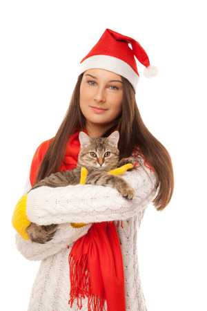 Beautiful young woman in santas hat with kitten on her hands photo