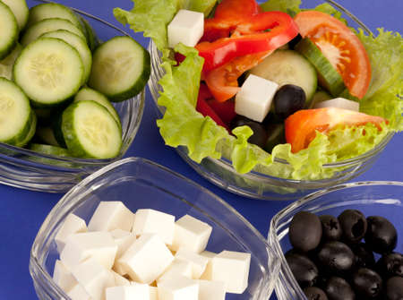 ingridients: Picture of plates with greek salad and ingridients on blue background Stock Photo