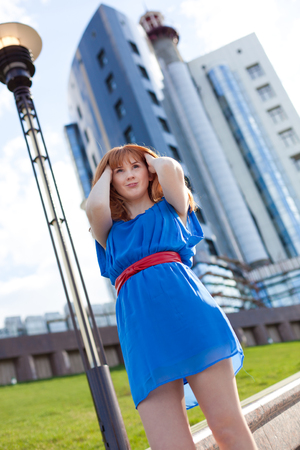 Beautiful ginger woman in blue dress and red belt against building photo