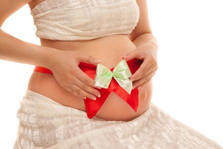 bow belly: Belly of pregnant woman with red ribbon and green bow