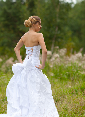 Picture of beautiful bride in white wedding dress in nature photo