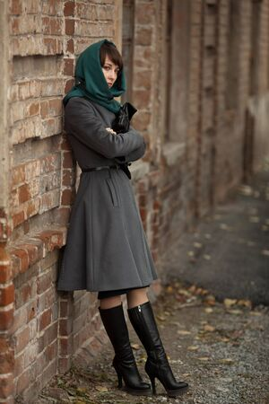 Schöne stilvolle Frau im grauen Mantel und schwarzen Handtasche im Freien