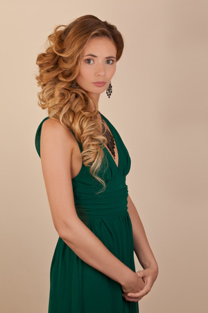 Blond beautiful wonan in green dress with curly hairstyle at studio photo