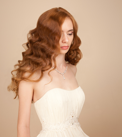 Portrait of bride with curly hairstyle and beautiful makeup looking down photo