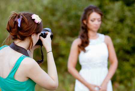 Picture of a woman photographer making a photo of a bride photo