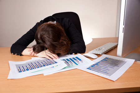 Sleeping businesswoman with financial report at office photo