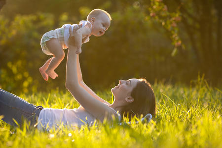Cute cheerful baby on mothers hands lying on grass