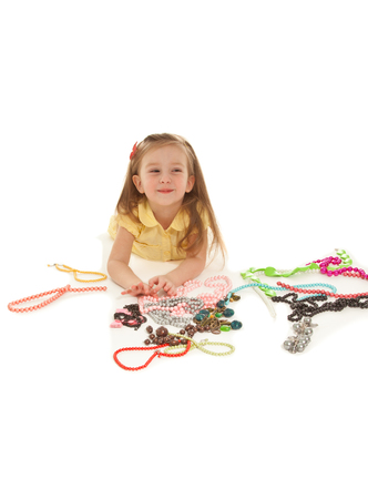 Little beautiful girl with a lot of jewelry isolated on white