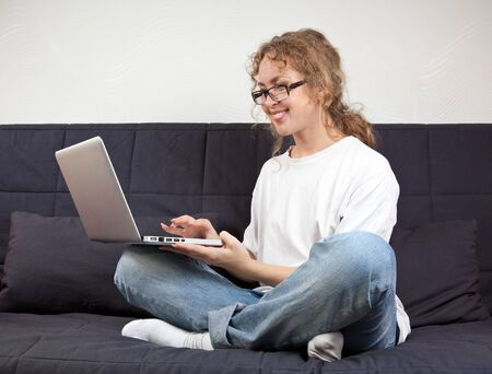 Beautiful freelancer woman with laptop sitting on the coach and working in the Internet