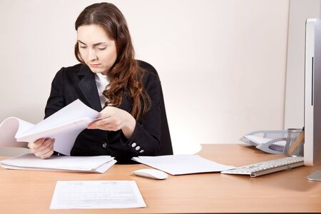 Beautiful businesswoman with financial reports at the office