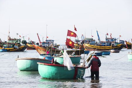 ne: Mui Ne, Vietnam - Feb 23, 2017. Fishing boats docking on the sea in Binh Thuan, Vietnam. Binh Thuan Province is known for its beaches and coastal roads.